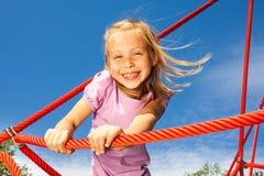 Lachendes Mädchen hält Seil und steht auf ihm im Park Lizenzfreie Stockfotos