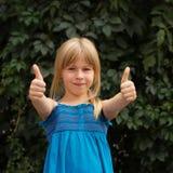 Lachendes Mädchen mit dem Gänseblümchen, das sich Daumen zeigt Lizenzfreie Stockfotografie