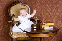 Lachendes Mädchen mit dem Telefon im Weinleseinnenraum Stockfotografie