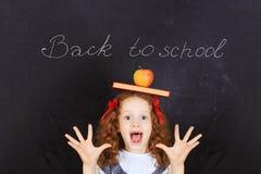 Lachendes Mädchen mit einem Buch und ein Apfel auf seinem Kopf Einfaches learnin Lizenzfreies Stockbild