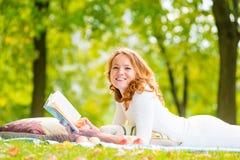 Lachendes Mädchen mit einem guten Buch auf dem Gras Stockfotografie