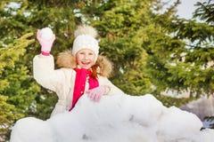 Lachendes Mädchen mit Schneeball hinter Schneewand Stockfotos
