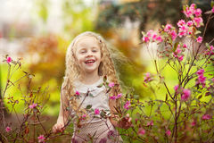 Lachendes Mädchen und rosafarbene Blumen Stockfotografie