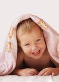 Lachendes Mädchen unter einer Decke lizenzfreie stockfotos