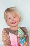 Lachendes schönes Mädchen, das ein Spielzeugfeuerrad hält Lizenzfreies Stockfoto