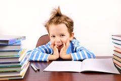 Lachendes Sitzen des netten Jungen am Schreibtisch Stockfotografie