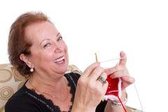 Lachendes sitzendes Stricken älterer Dame Stockfotos