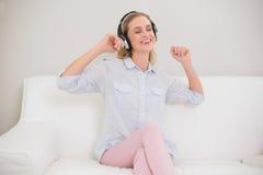 Lachendes zufälliges blondes Hören Musik Stockfotos