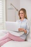 Lachendes zufälliges blondes Sitzen auf Couch unter Verwendung des Laptops Stockfoto