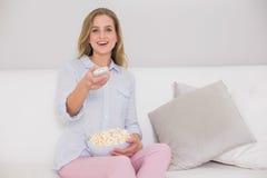 Lachendes zufälliges blondes Sitzen auf der Couch, die Direktübertragung hält Stockfoto