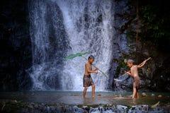 Lachenfischen mit zwei Jungen an einer Wasserfalllandschaft Thailand Fishin Stockfoto