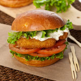 Lachsburger mit Kopfsalat und Weinstein Stockfotografie