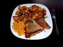 Lachse mit Ofenkartoffeln und Mais Stockfotografie