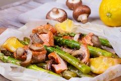 Lachse, Spargel, Pilze und Zitrone im Pergament Lizenzfreies Stockfoto