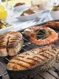 Lachse und Garnelen, die auf einem Grill kochen Stockfotos