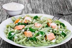 Lachse und Spinat Fettuccineteigwaren auf weißen Tellern stockbild