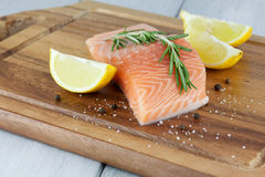 Lachsfilet. Fresh salmon with lemon and rosemary on a wooden board Royalty Free Stock Photos