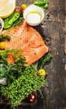 Lachsfilet mit Öl und frischen Bestandteilen für das Kochen auf rustikalem hölzernem Hintergrund, Draufsicht stockbild