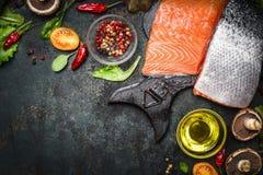 Lachsfilet mit köstlichen Bestandteilen für das Kochen auf dunklem rustikalem hölzernem Hintergrund, Draufsicht, Rahmen Stockbild