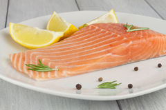 Lachsfilet. Salmon on a plate with rosemary and fresh lemon Royalty Free Stock Photos