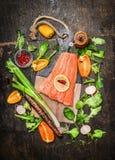Lachsfischfilets auf Schneidebrett mit Frischgemüse und Gewürzbestandteilen auf rustikalem hölzernem Hintergrund, Draufsicht Lizenzfreie Stockbilder