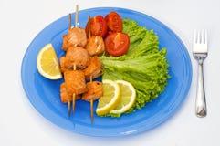 Lachskebab mit Kopfsalat, Zitrone und Kirsche auf blauer Platte Stockfotos