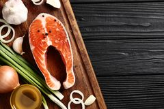 Lachssteakpfeffer- und -salzkräuter auf schwarzer Tabelle lizenzfreie stockbilder