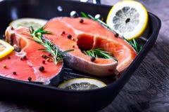 Lachssteaks in einer Grillwanne mit Zitrone, Kräutern und Gewürzen Lizenzfreie Stockfotos
