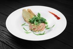 Lachstartare mit Avocado auf weißer Platte Stockfotografie