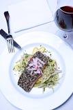 Lachsteller auf weißer Tischdecke mit Glas Rotwein Lizenzfreies Stockfoto