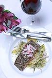 Lachsteller auf weißer Tischdecke mit Glas Rotwein Lizenzfreie Stockfotos