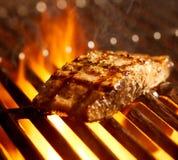 Lachsverkleidung auf dem Grill mit Flammen Stockfotografie