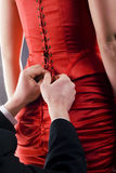 Lacing. Man is lacing a corset of a red dress Royalty Free Stock Image