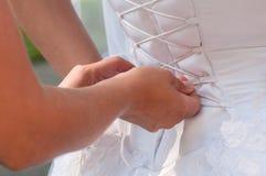 Lacing up brides corset. Assistant girl lacing up brides white corset. Horizontal shot Stock Photo