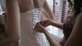 Lacing up a corset of a wedding dress stock video