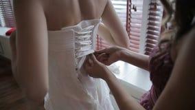 Lacing up a corset of a wedding dress. Close up stock video