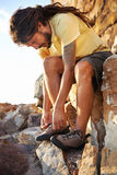 Lacing up. Hiker with dreadlocks tying his shoelaces Royalty Free Stock Photo