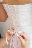 Lacing up a wedding dress stock photo