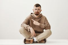 Lack of attention makes him miserable. Cute stylish urban guy with beard and glasses sitting with crossed legs on floor. Crying or whining, pointing left royalty free stock image
