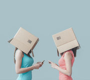 Lack of communication. Adolescent girls with boxes on their heads texting with their smart phones, social networks and isolation concept Royalty Free Stock Images