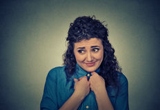 Lack of confidence. Shy young woman feels awkward. On gray wall background. Human emotion body language life perception Royalty Free Stock Images