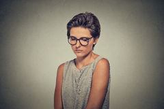 Lack of confidence. Shy young woman in glasses feels awkward. On grey wall background. Human emotion body language life perception Royalty Free Stock Photos