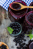Ð'lack currant jam on the table. Ð'lack currant jam on the old table royalty free stock image