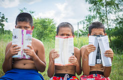 Lack of education. Poverty countryside of boys sitting together with boock covering books , lack of education concept stock images