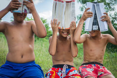 Lack of education. Poverty countryside of boys sitting together with boock covering books , lack of education concept royalty free stock photo