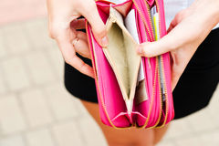 Lack of money. Woman opens an empty wallet Stock Images