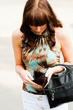 Lack of money. Woman looks at an empty wallet Royalty Free Stock Images