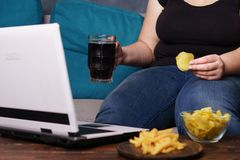 Lack of physical activity, laziness, homebody. Lack of physical activity, remote work, laziness, homebody. Lonely woman watching series at laptop drink beer eat royalty free stock photo