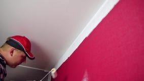 Lack-Rolle mit Lackproben Ein Mann in einem roten Hut, der einen Raum mit einer Farbenrolle und -Pinsel färbt stock video