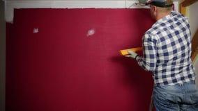 Lack-Rolle mit Lackproben Ein Mann in einem roten Hut, der einen Raum mit einer Farbenrolle und -Pinsel färbt stock video footage